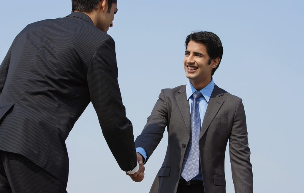 networking skills - man shaking hands in confidence to make an impression