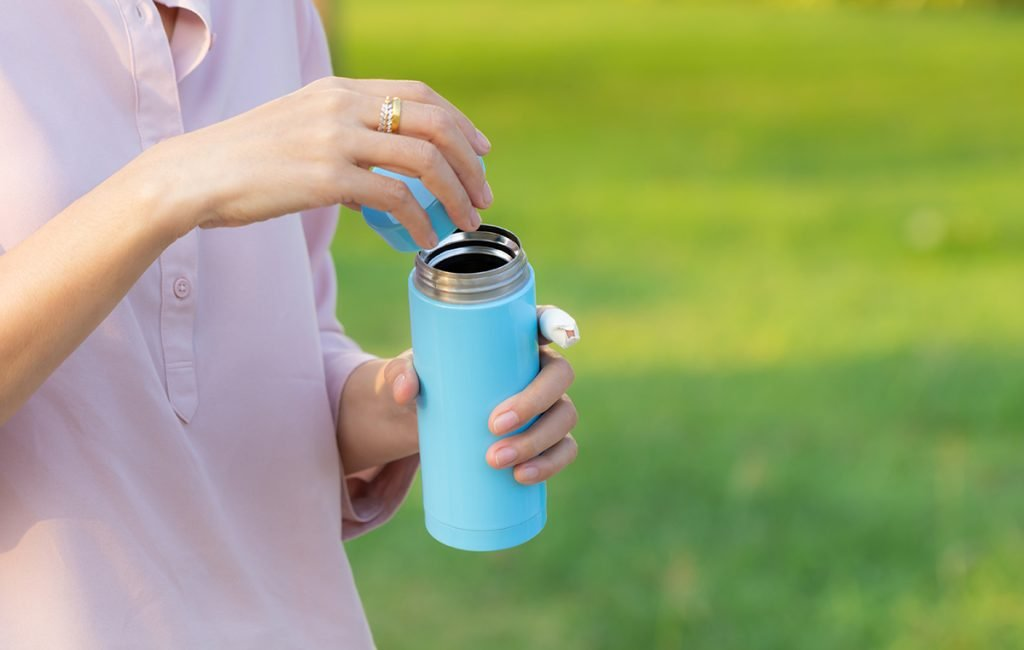 Drinking Water: Girl opens the cap of a water bottle
