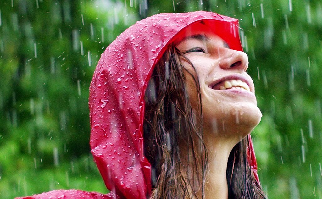 monsoon skincare: An image of a girl getting wet in the rain
