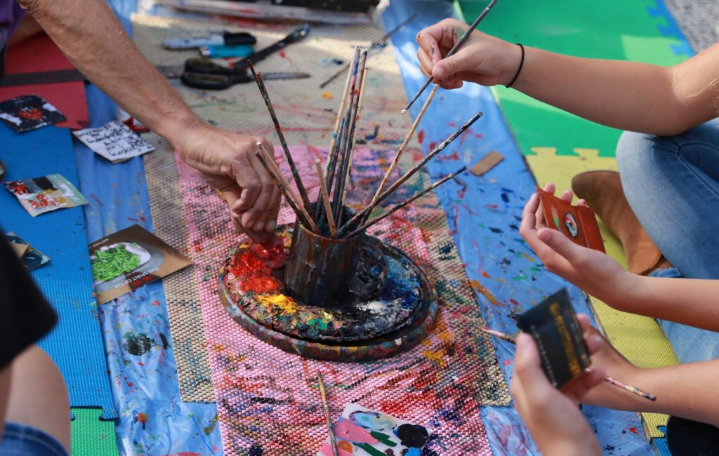 Friendship Day 2019: Hands of people with paint brushes at a workshop
