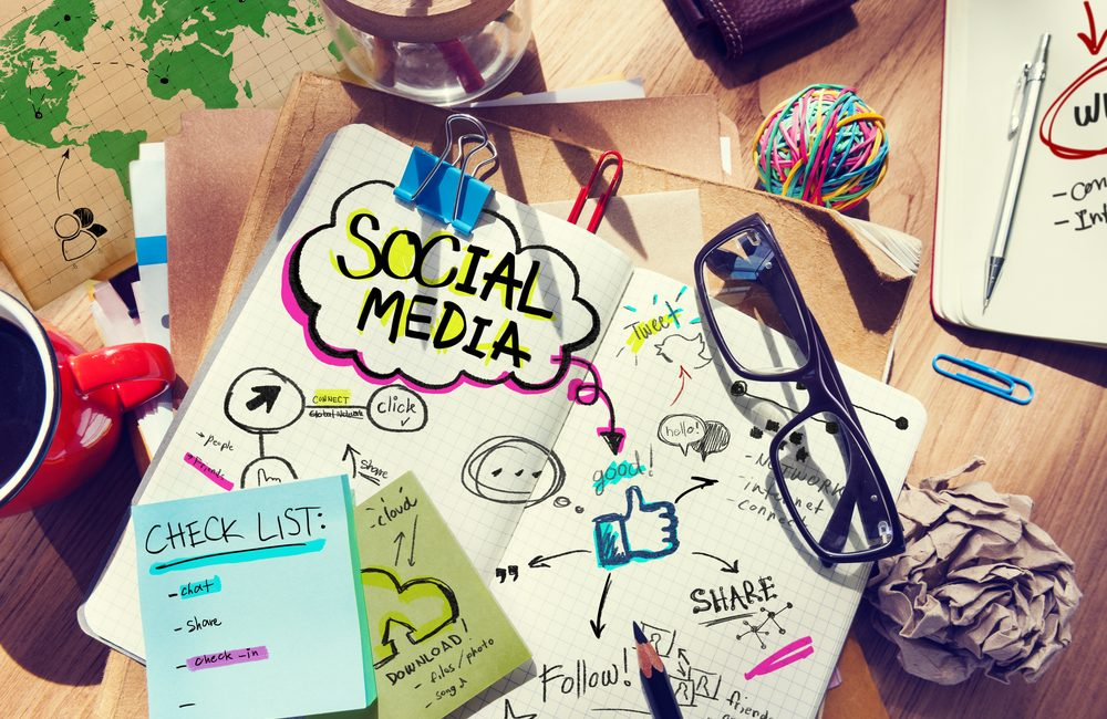 QNET's Social Media Policy: The various features of social media written on a notebook
