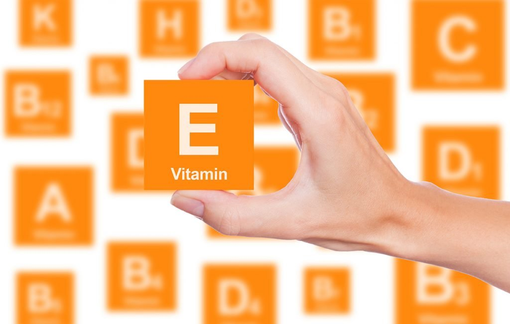 vitamin e for skin: hand holding an orange block with the text vitamin e on it