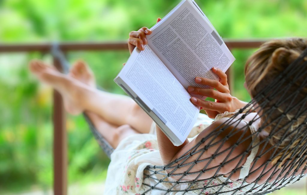 Woman relaxing on a hammock are reading a book