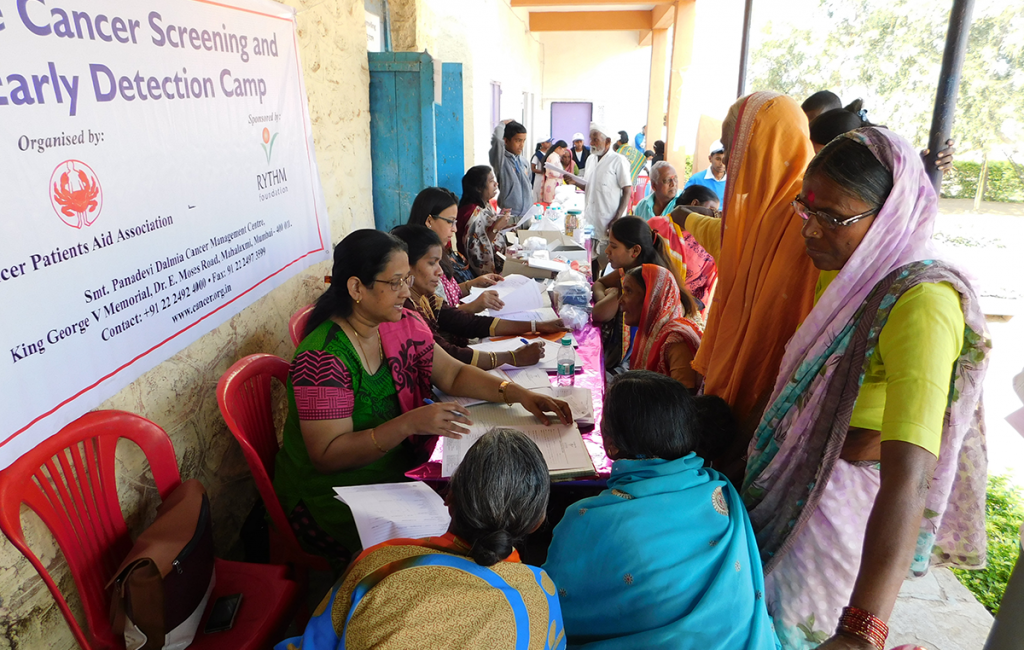 RYTHM Foundation: Locals gathered around registration desk at Cancer screening and early detection camp