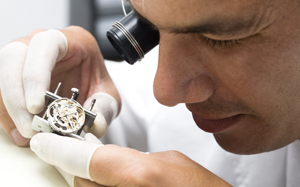 watchmaker inspecting swiss movement