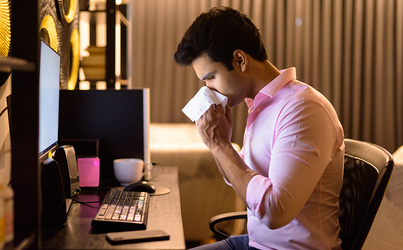 Indian man sneezing into a white cloth while working in front of a computer due to allergy.